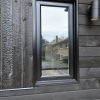 framed with an exterior welded trim - black finish - against charred cedar siding